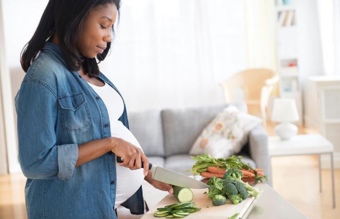 Pregnant woman chopping vegetables