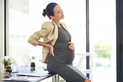 Pregnant businesswoman in discomfort in her office