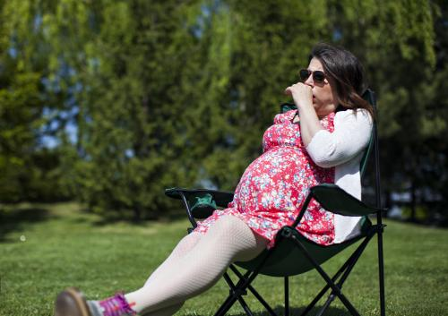 Pregnant woman outdoors coughing