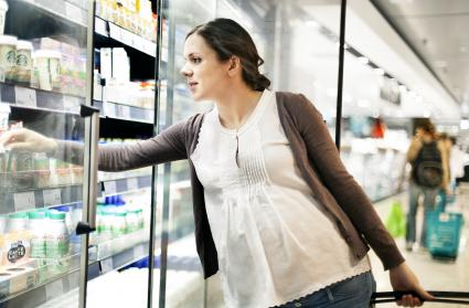 Pregnant woman in supermarket buying groceries
