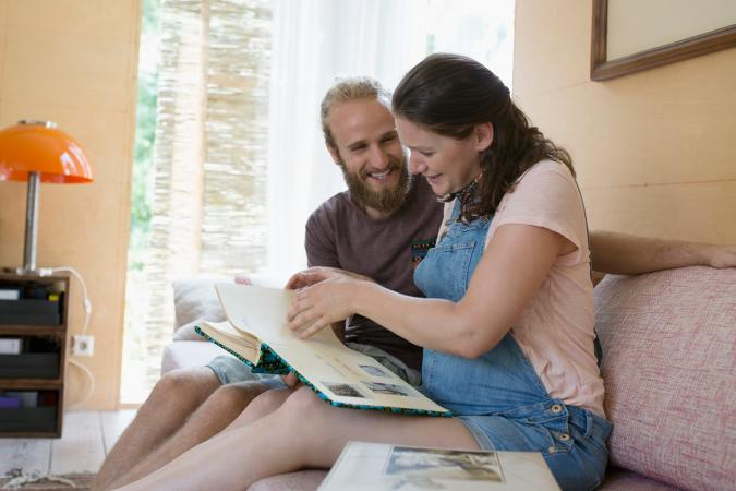 Pregnant couple looking at scrapbook