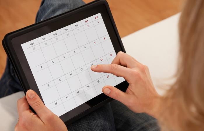 woman using calendar on digital tablet