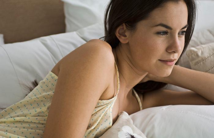 Woman reclining in bed contemplatively looking away