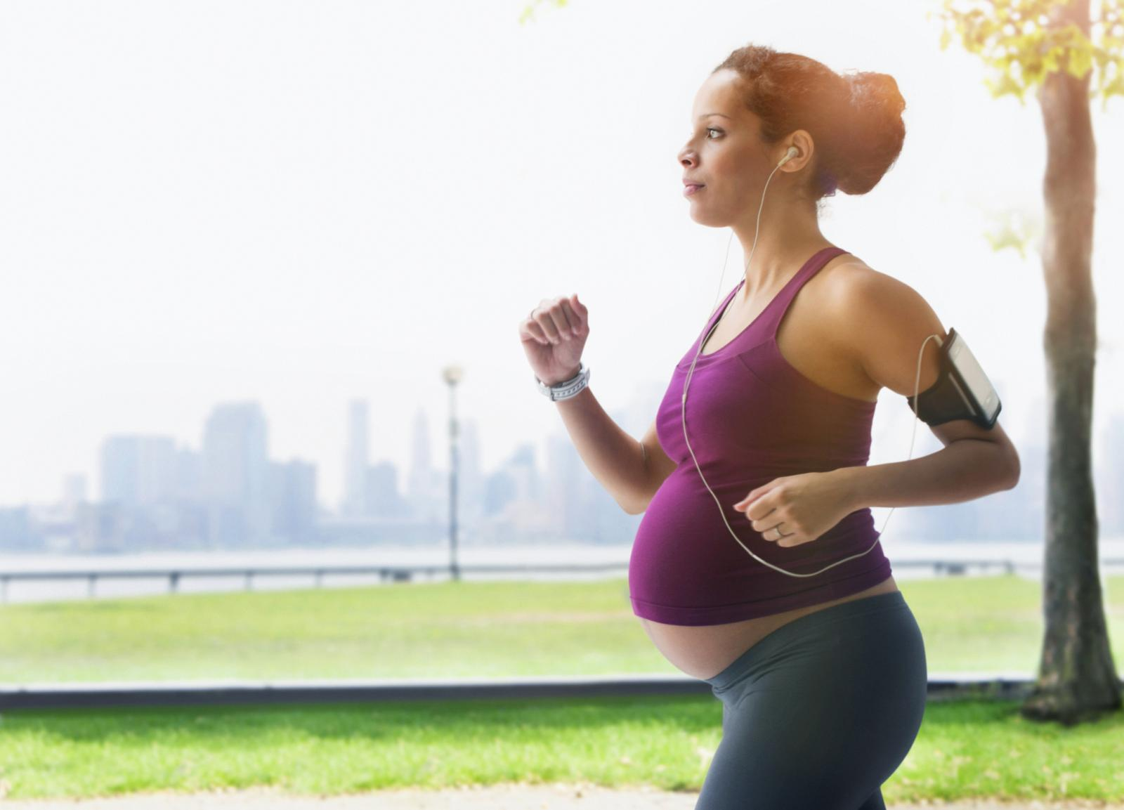 Pregnant woman power walking in park