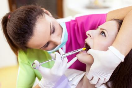 Woman dentist giving her patient an anesthesia injection