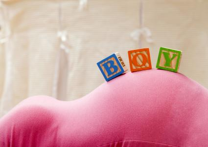 Wooden blocks with letters on pregnant woman's belly, reading as boy