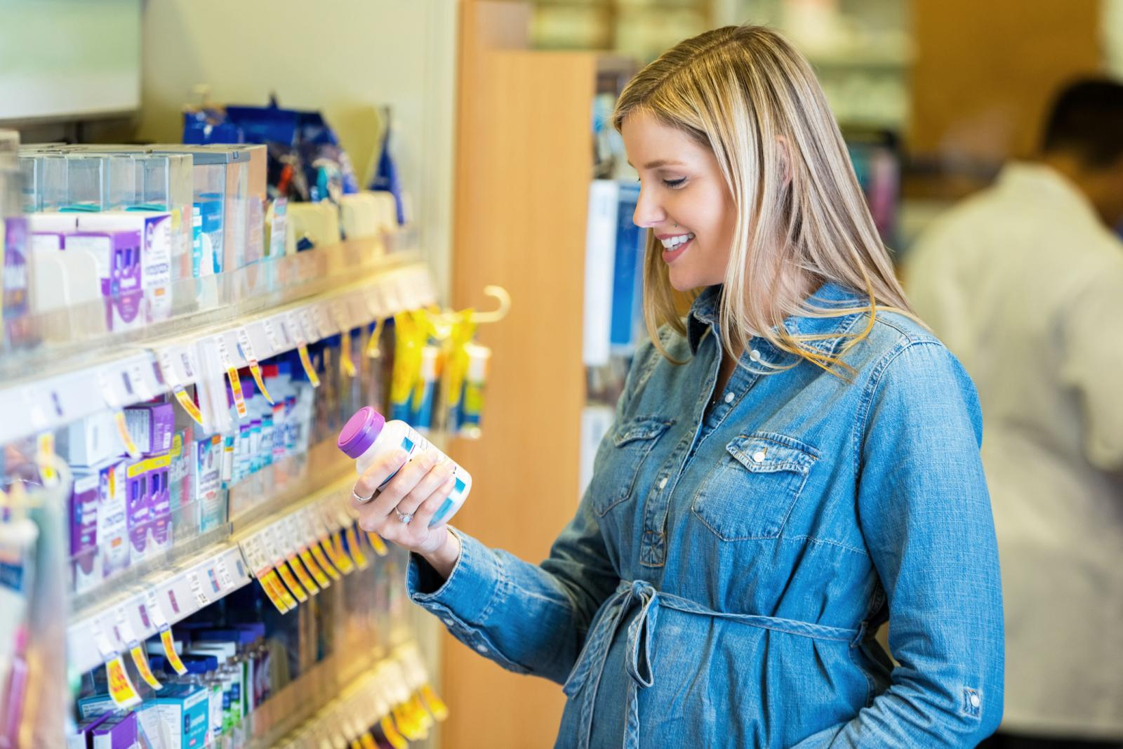 Pregnant woman reading prenatal vitamin label in pharmacy
