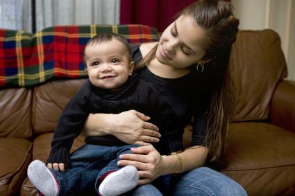 Adorable Baby Boy Sitting on Mother's Lap at Home