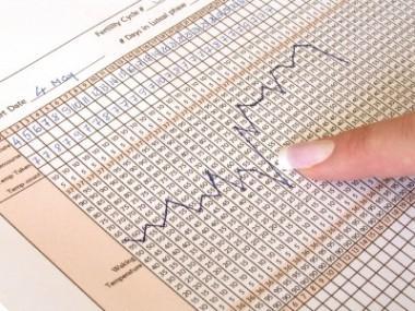Woman examining her basal body temperature chart