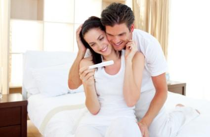Happy couple looking at a positive pregnancy test