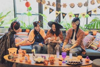 Young group having a Halloween party and playing a game around a table