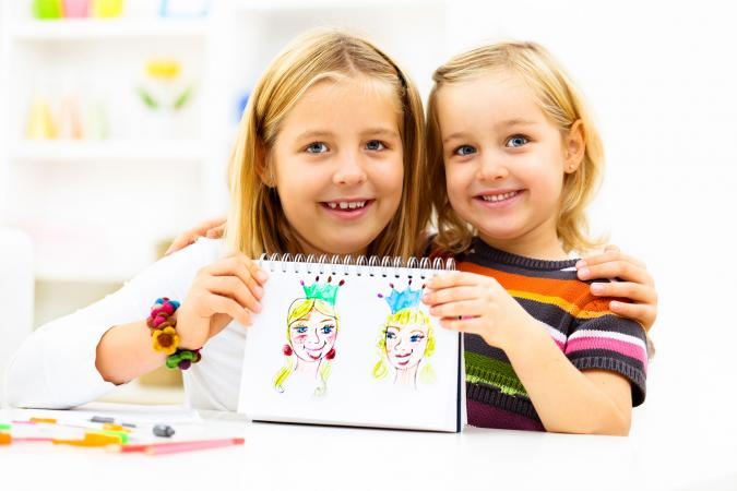 Two girls holding princess drawings
