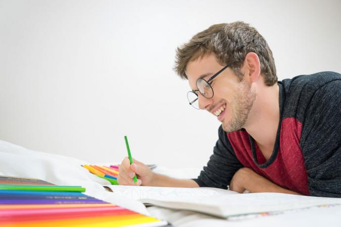 Young man smiling while coloring pages