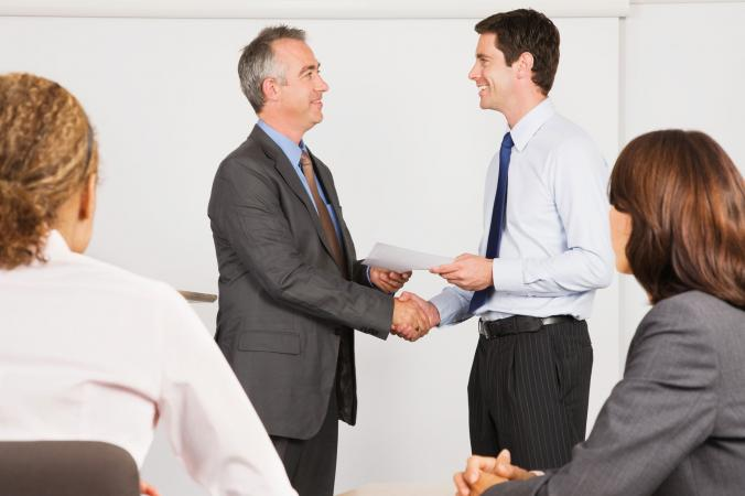 Businessman giving gift certificate to employee