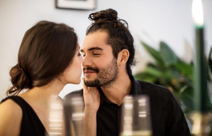 Pareja besándose durante la cena