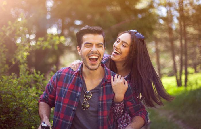 Pareja alegre andando en bicicleta juntos