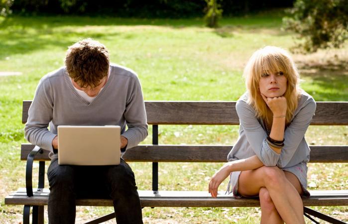 Hombre en la computadora y mujer infeliz