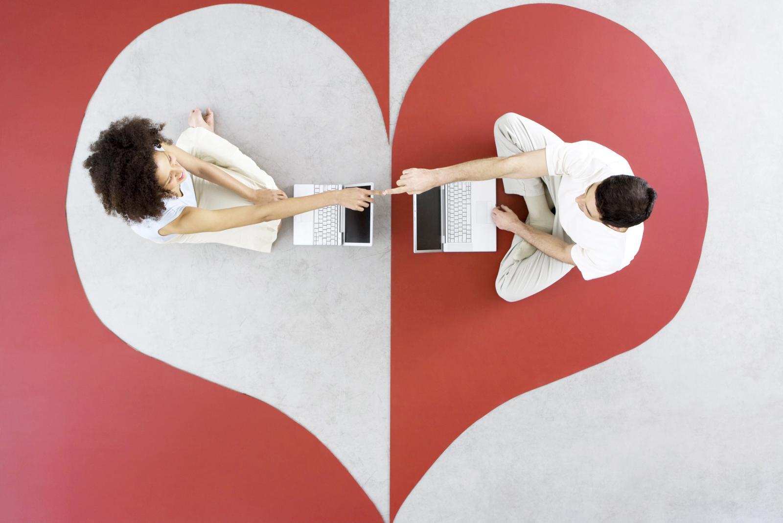 Pareja sentada con en el suelo dentro de un corazón con sus ordenadores