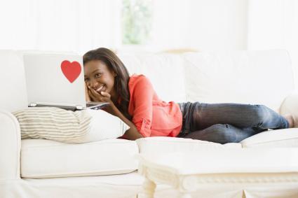 Mujer usando el ordenador tumbada en el sofá