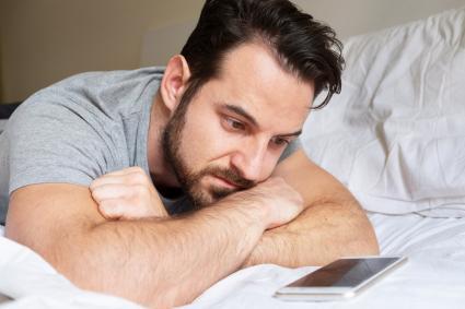 Hombre en la cama mirando al movil, esperando una llamada
