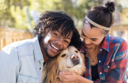 Pareja alegre jugando con perro