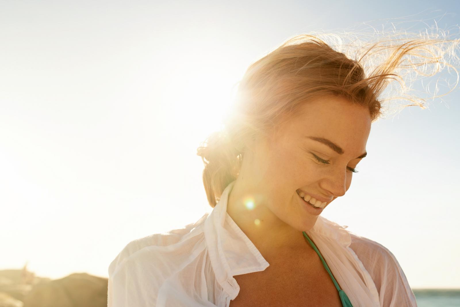 Mujer en la playa sonriendo