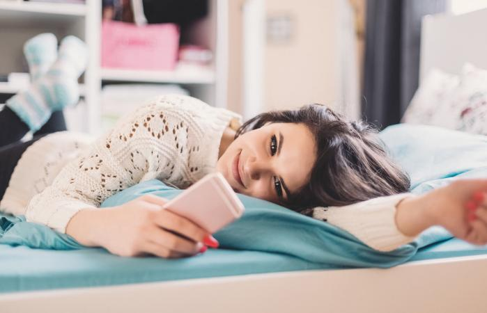 Chica adolescente usando teléfono móvil