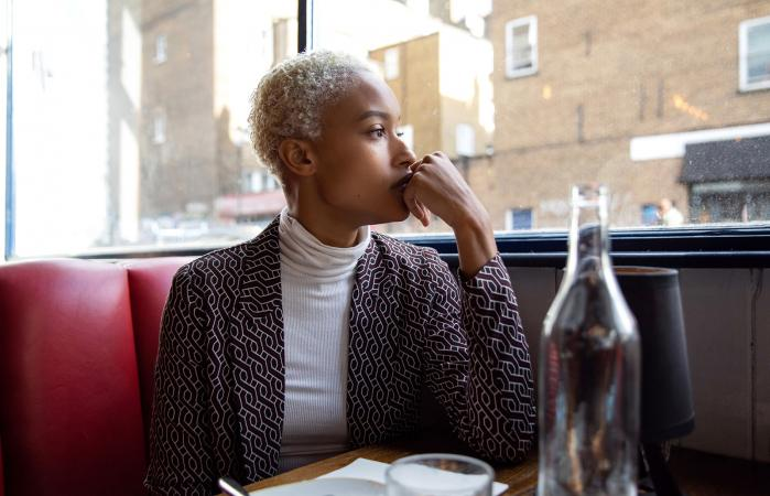 Mujer pensativa mirando por la ventana