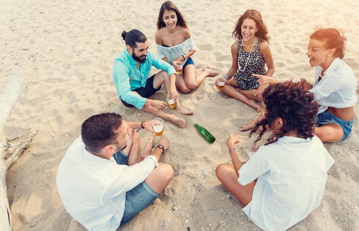 Grupo de amigos jugando a girar la botella en la playa