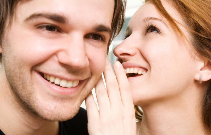 Mujer susurra al oído del hombre