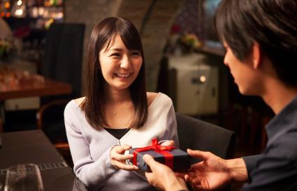 Mujer dando a un hombre una caja de chocolates