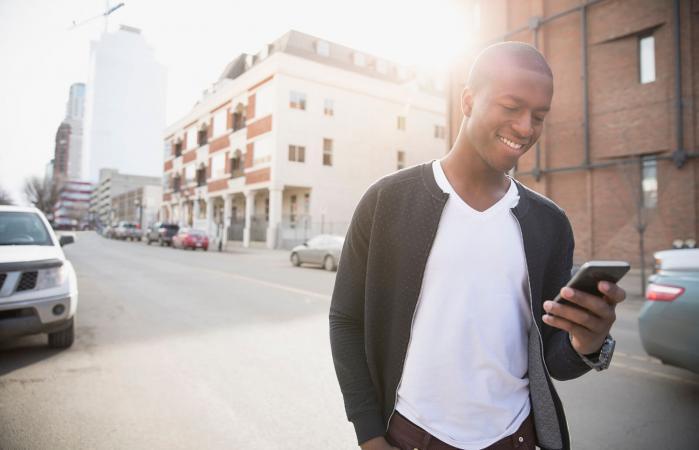 Hombre sonriente enviando mensajes de texto