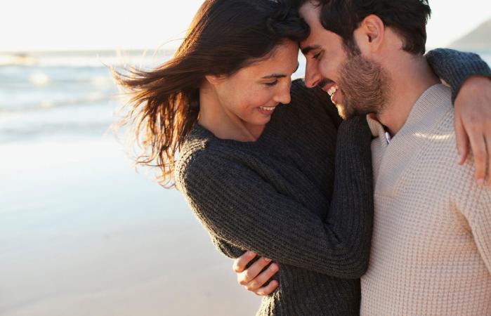 Pareja sonriente abrazándose en la playa