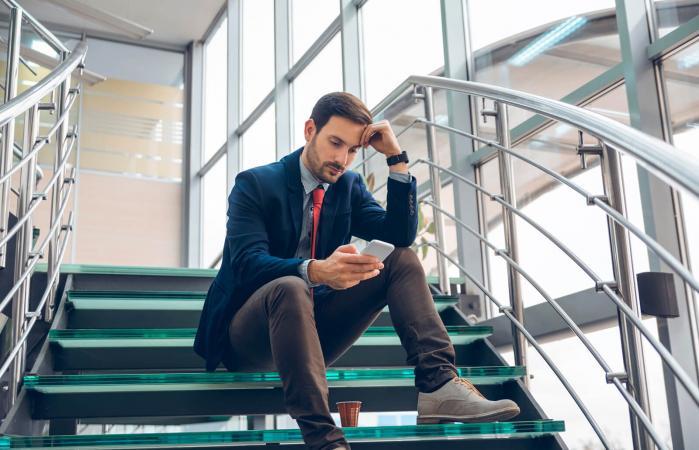 Hombre pensativo mirando el teléfono celular