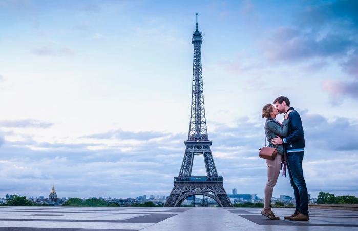 Pareja besándose cerca de la Torre Eiffel