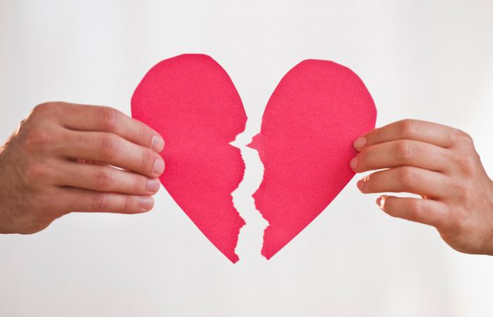 Dos manos sosteniendo un corazón de papel roto