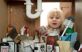 little girl reaching under sink
