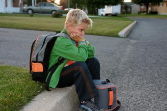 Young boy sitting on curb