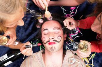 Girls putting makeup on sleeping friend