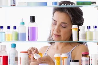 Hispanic woman taking medication in bathroom