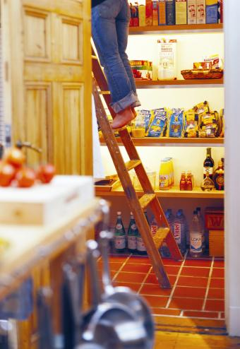 Woman standing on ladder in pantry