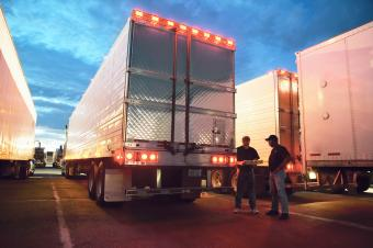 Two truck drives checking dispatch papers