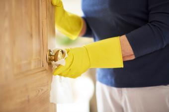 Mature woman wiping down a doorknob