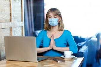 woman with surgical medical mask is sitting and working on laptop and try to relax