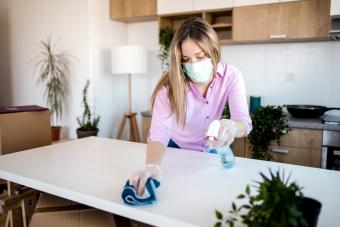 Young woman wearing mask for protection while cleaning