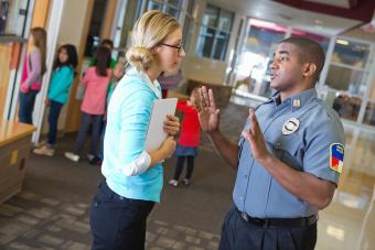 Police officer talking to teacher outside her classroom