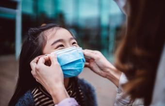 Mom helping daughter to wear face mask