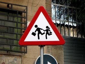 children running school crossing sign