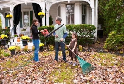 A family raking leaves