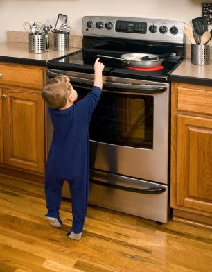 Toddler reaching for a hot stove on the pan